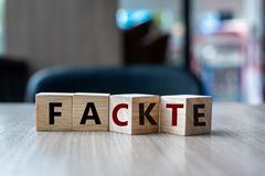 Wooden cube with flip over block FAKE to FACT word on table background. News, solution and business concepts stock photo