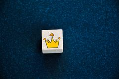 King`s Crown. Wooden cube with a hand  painted  crown  on    black background Greeting card background Stock Photo