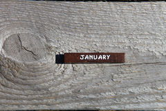 Wooden cube with the name of the month at the old board. January Stock Photos