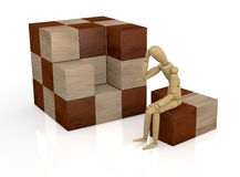 Wooden cube puzzle. One wooden dummy that thinks how to solve a cube puzzle (3d render Royalty Free Stock Photo