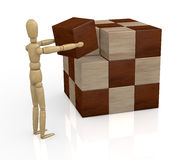 Wooden cube puzzle. One wooden dummy that solves a cube puzzle (3d render Stock Photography