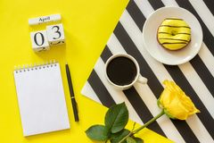 Wooden cubes calendar April 3rd. Cup of coffee, yellow donut and rose on black and white napkin, empty open notepad for stock photography