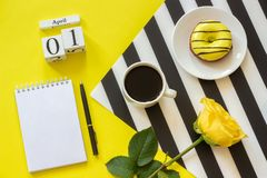 Wooden cubes calendar April 1st. Cup of coffee, yellow donut and rose on stylish black and white napkin, empty open royalty free stock photography