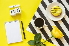 Wooden cubes calendar April 6th. Cup of coffee, yellow donut and rose on black and white napkin, empty open notepad for royalty free stock photos