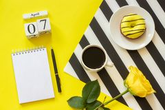 Wooden cubes calendar April 7th. Cup of coffee, yellow donut and rose on black and white napkin, empty open notepad for royalty free stock photos