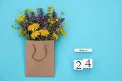 Wooden cubes calendar August 24 and field colorful rustic flowers in craft package on blue background. Greeting card Flat Lay. Concept Hello August Template stock photos