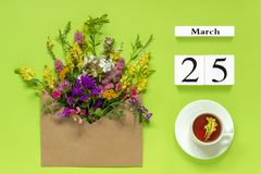 Wooden cubes calendar March 25. Cup of herbs tea, kraft envelope with multi colored flowers on green background. Concept hello royalty free stock image