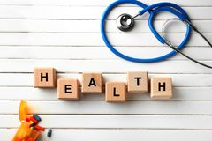 Wooden cubes composed word HEALTH on white table stock images