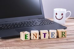 Wooden cubes enter word. With laptop and happy face mug on wooden table royalty free stock photo