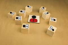 Wooden cubes in the form of bosses and subordinates, personnel subordination on a blue background. Business situation rules employee job leader leadership stock photography