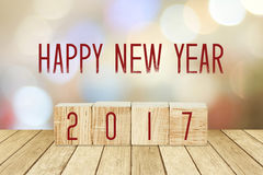 Wooden cubes with 2017 and happy new year over blur bokeh backgr Stock Image