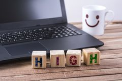 Wooden cubes high word. With laptop and happy face mug on wooden table Royalty Free Stock Photography