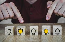 Wooden cubes with the image of a light bulb that symbolizes a new idea, concepts of innovation and solutions, 2 of which poke a royalty free stock photography