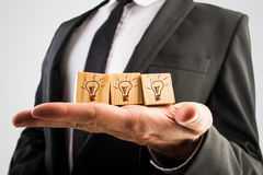 Wooden cubes with incandescent light bulbs. Businessman holding three wooden cubes with incandescent light bulbs conceptual of inspiration, creative ideas and Stock Photography