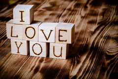Wooden cubes with inscription I LOVE YOU on new wooden background. Selective focus. Toned Stock Photo