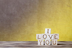Wooden cubes with inscription I LOVE YOU on new wooden board and burlap background Royalty Free Stock Image