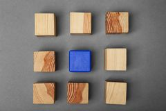 Wooden cubes and one different. On grey background Stock Images