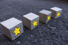 4 wooden cubes with a pattern of a yellow star standing on top of each other on asphalt
