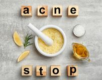 Wooden cubes with phrase. `Stop acne` and homemade effective problem skin remedies on grey background, flat lay Stock Images