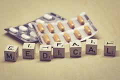 Wooden cubes showing the word medical, pills in background stock images