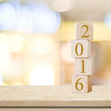Wooden cubes with 2016 on table over blur background, new year t Stock Photos