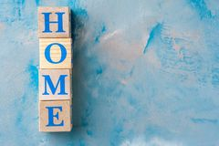 Wooden cubes with word HOME on blue table. Cubes with blue letters. Free space for design stock photography