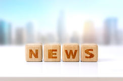 Wooden cubes word news concept. Wooden cubes message word news on white table city view.Advertisement design concept.Morning daily news symbol stock image
