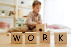 Wooden cubes with word WORK in hands of little boy. Wooden cubes with word WORK in hands of happy smiling little boy at home. Conceptual image about child rights stock photo