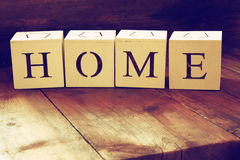 Wooden cubes with the writing home over wooden table. Royalty Free Stock Photos