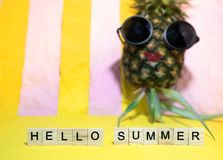 Wooden cubes with written words Hello summer and red lip pineapple wears sunglasses, having sun bath on bright yellow and pink pa. Stel stripe background royalty free stock photography