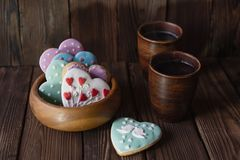 Wooden cup with glazed gingerbread hearts and mugs of tea stock photography