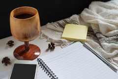A wooden cup of juice, paper note, note book, smartphone. On the table with black background stock photos