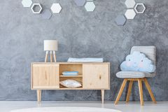 Chair in baby room. Wooden cupboard and chair with a cloud-shaped pillow in a baby room interior with honeycomb decoration on the wall Royalty Free Stock Photo