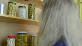 Wooden cupboard jars. Blonde girl puts jars of canned cucumbers and peppers in a wooden cupboard stock footage
