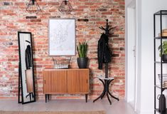 Wooden cupboard with plant on it between mirror and black hanger. Real photo stock photo
