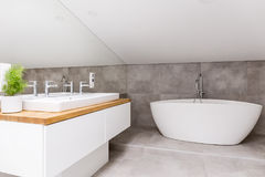 Bathroom with shaped bathtub. Wooden cupboard with sink and faucet in bathroom with shaped bathtub and mirror royalty free stock images
