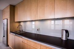 Wooden cupboards and black worktop. In modern kitchen stock photos