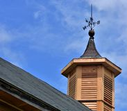 Wooden Cupola on old barn with weathervane on top. Blue skies white wispy clouds sunny new wood siding summer time Stock Photos