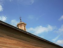 Wooden Cupola on old barn with weathervane on top. Blue skies white wispy clouds sunny new wood siding summer time Middlesex County Massachusetts USA stock photo