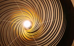 Wooden curve line lamp with lighted bulb in the center.  stock photography
