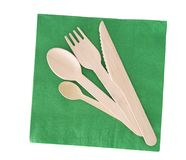 Wooden cutlery, fork, spoon, knife with green paper napkin isolated on white. Alternative to plastic royalty free stock photos