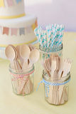 Wooden cutlery and paper straws in jam jars tied with kitchen twine stock photos