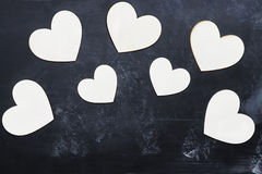 Wooden Cutout Valentine`s Day Hearts over Blackboard Stock Images