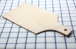 Wooden cutting board. On a checkered tablecloth royalty free stock image