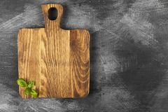 Wooden Cutting Board And Leaves Of Basil On Dark Background. Top Stock Photography