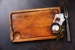 Wooden cutting board background with seasoning, herbs and kitchen fork on dark background copy space stock photos