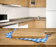 Wooden cutting board, blue checkered towel over blurred kitchen background Stock Photos