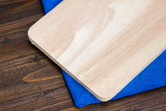 Wooden cutting board and blue cloth on wood table background. Wooden cutting board and blue cloth on wood table for background Royalty Free Stock Photo