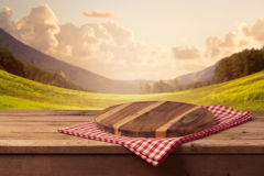 Wooden cutting board with checked tablecloth on table over landscape background Royalty Free Stock Images