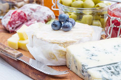 Wooden cutting board with cheese, cold cuts and jams Stock Photos